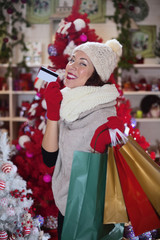 happy woman showing gifts bought with a credit card