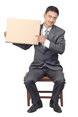Sitting young man pointing in blank cardboard