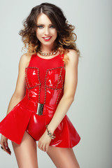 Glamor. Smiling Sensual Woman in Red Shiny Clothes