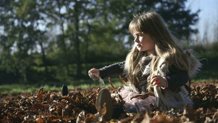 Little girl playing outdoors in autumn park.