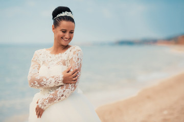 Beautiful bride on the beach in wedding dress