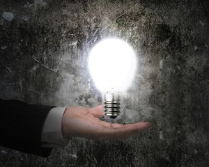 human hand holding brightly light bulb illuminated dark old wall