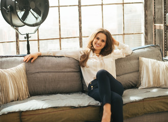 Relaxed young woman sitting on couch in loft apartment