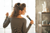 Fototapeta Young woman singing with microphone. rear view
