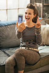 Cheerful young woman making selfie in loft apartment