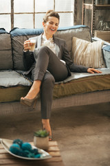 Happy business woman with coffee latte in loft apartment