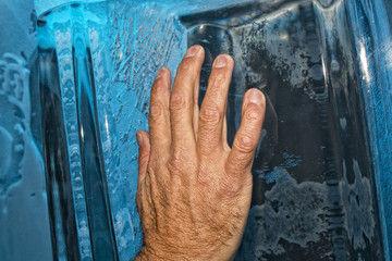 Hand on ice blocks wall