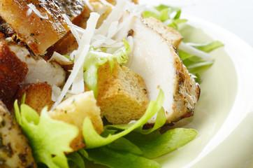 Caesar chicken salad on white table