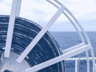 Ship winch with cable and ocean in the background