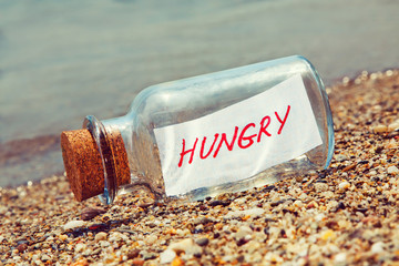Message in a bottle saying Hungry. Hunger concept.