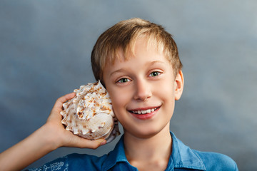 Funny child holding sea shell smiling. Vacation concept.