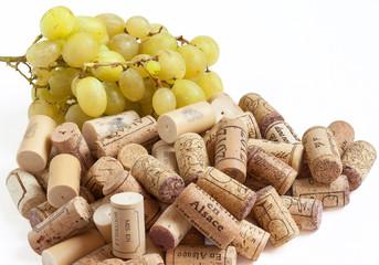 Bouchons de liège et grappe de raisin en vrac sur fond blanc