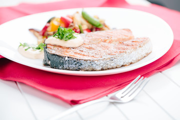 Grilled Salmon with Fresh vegetables on red background