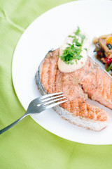 Grilled Salmon with Fresh vegetables on green background