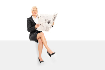 Businesswoman reading the news seated on a panel