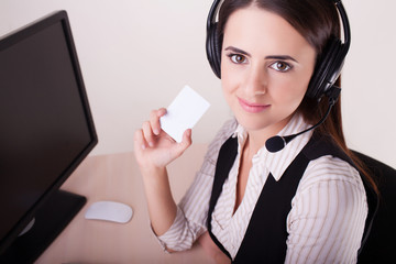 Call center woman with headset showing business card.