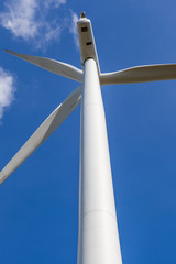 Looking up the wind turbine against blue sky background in wind