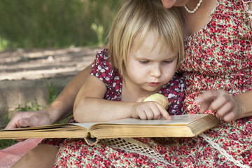 Girl reading a book on his mother's lap