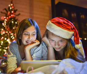 Christmastime, two smiling young girls in pajamas lying on the f