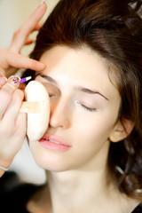 Beautiful fashion female model getting makeup