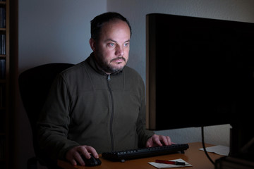 man sitting in front of computer at night