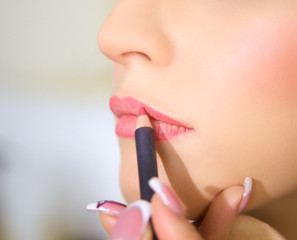 Closeup of lips getting red lipstick
