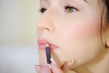 Woman getting pink lipstick on beautiful lips