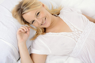 Frau im Nachthemd liegt im Bett