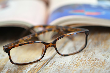 Reading glasses and open book on rustic wooden surface