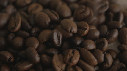 Roasted coffee beans. Falling coffee beans. Close-up.