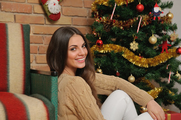 happy smiling young woman with presents near Christmas tree at h