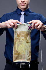 Young businessman is knitting a euro banknote