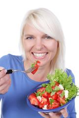 Hübsche blonde Frau isst Tomatensalat mit Mozarrella