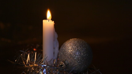 Burning big candle and Christmas Christmas tree decorations in f