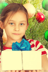 cute kid holding a box with Christmas present on background of N