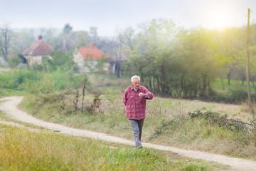 Senior man walkng in village