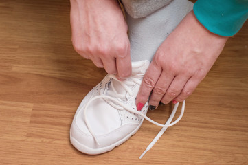 Process of clothing of white sports sneakers