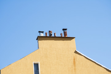 Chimney section of yellow housewall with different chimney caps