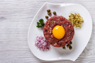 Beef tartare with egg close up on the table. top view
