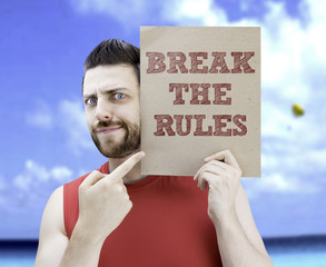 Man holding a card with the text Break The Rules