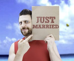 Man holding a card with the text Just Married