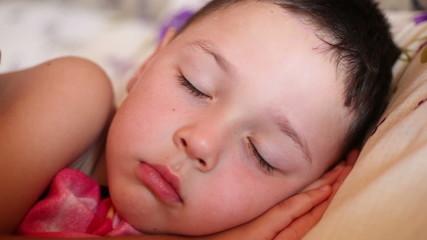 little boy falls asleep in bed