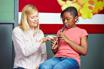 Lehrer hilft Kind beim Flöte spielen