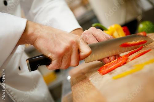 Papiers peints Cuisine closeup on hands cutting yellow pepper