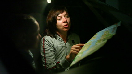 woman with her son on the road looking for a map at night 2