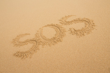 SOS - Inscription on the sand of tropical beach