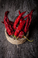 bunch of red hot peppers lying in a wicker basket on old wooden