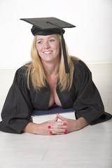 Female mature university student wearing cap and gown