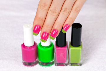 Female hand with a two-color manicure touch the nail polish