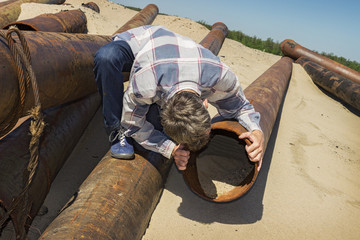 Curious young man looks into pipe